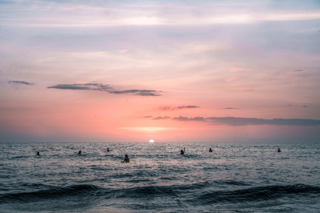 anonymous travelers swimming in wavy sea at sundown